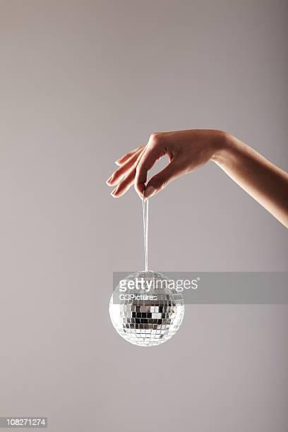 Femme mains tenant la boule à facettes