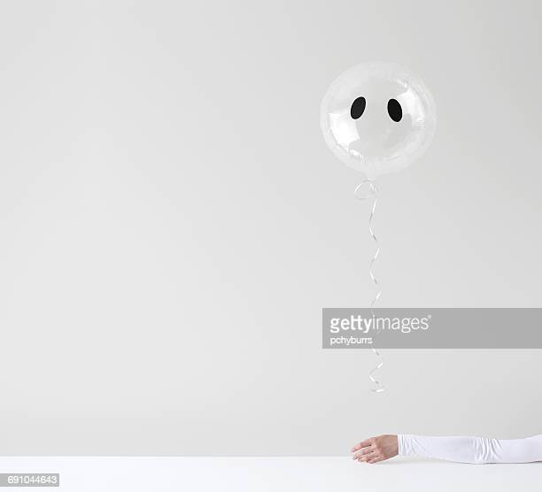 Woman's hand holding a Ghost balloon