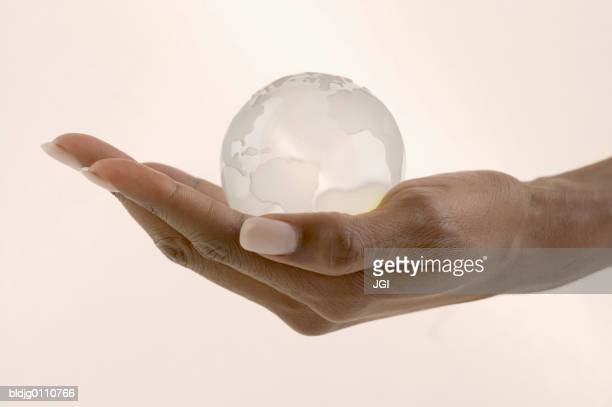 Woman's hand holding a glass globe in the palm of her