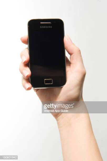 A woman's hand holding a Samsung Galaxy Ace smartphone during a studio shoot for Android App Guide February 11 2011