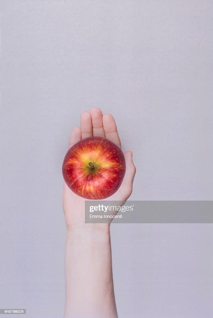 Woman's hand holding an apple