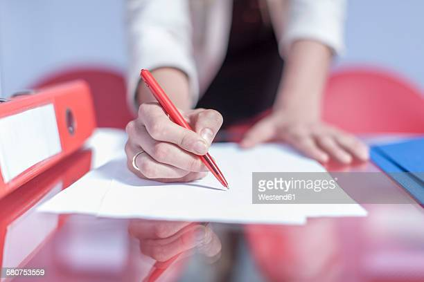 Womans hand holding ballpen for writing down something in an office