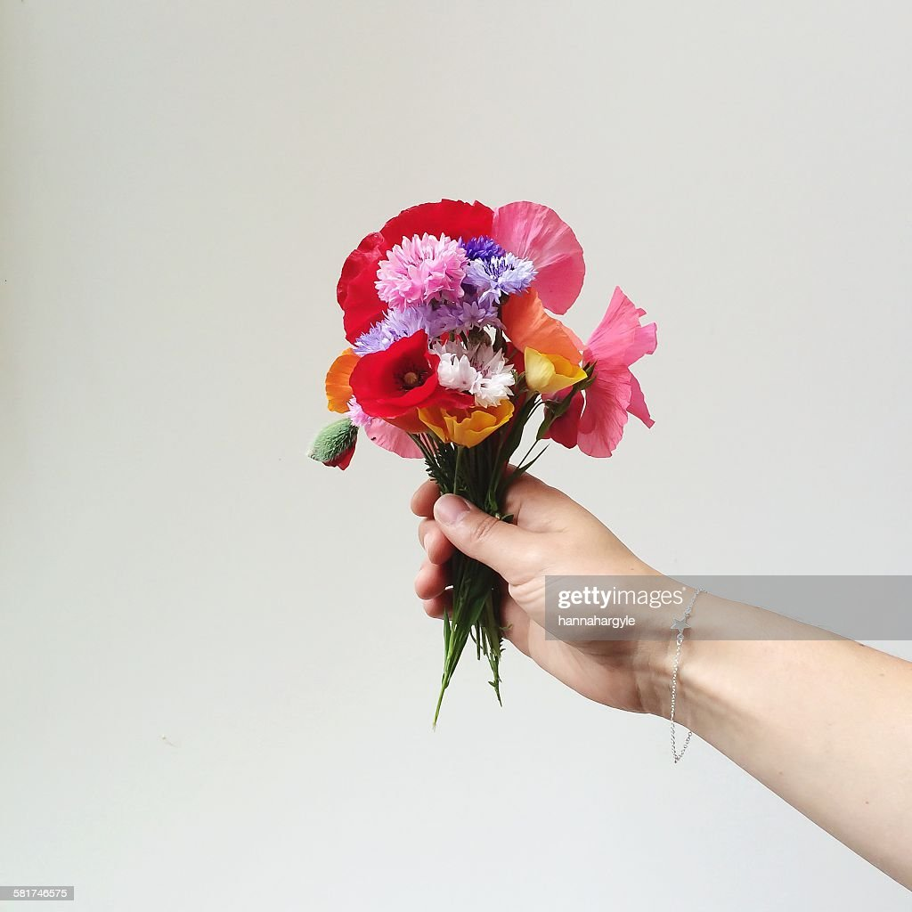 womans hand holding bunch of wildflowers