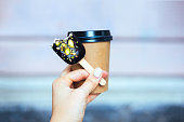 Woman's hand holding chocolate popsicle ice cream and coffee cup