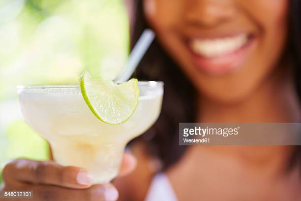 Womans hand holding cocktail glass decorated with slice of lime