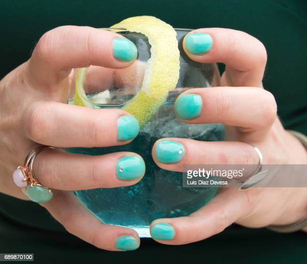 Woman's hand holding Cocktail  with green nails