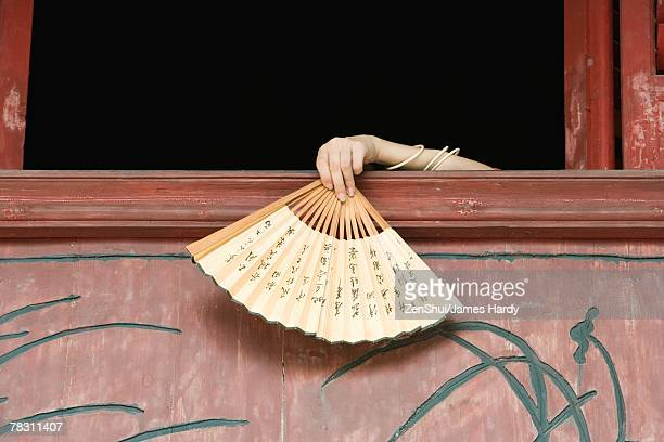 Woman's hand holding fan over edge of windowsill