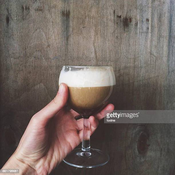 Womans hand holding glass of irish coffee drink