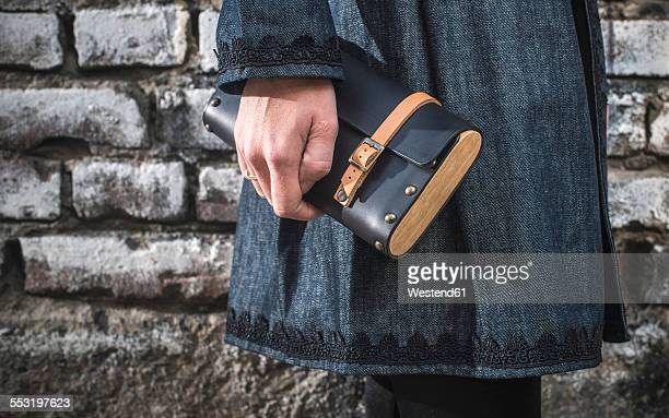 Womans hand holding leather handbag
