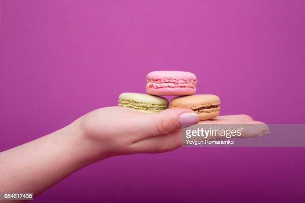 Woman's hand holding macaroons or macarons dessert on purple background