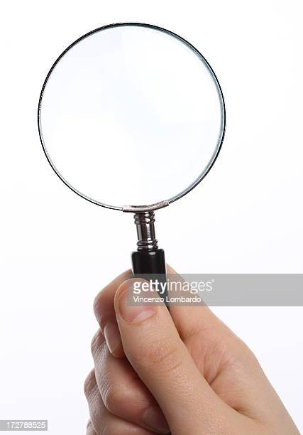 Woman's hand  holding  magnifying glass