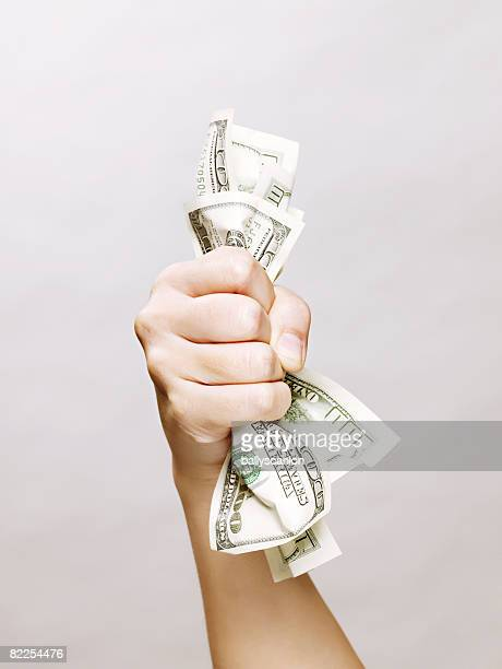 Woman's hand holding one hundred dollars bills