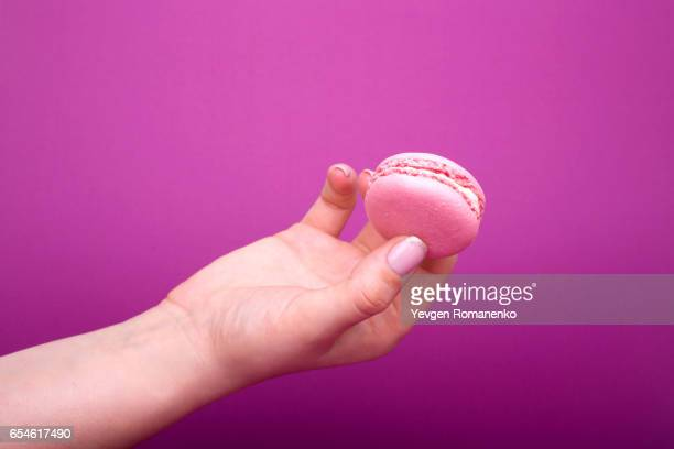 Woman's hand holding pink macaroon or macaron dessert on purple background