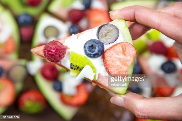 Woman's hand holding Pizza Slice made with fresh fruits. Fruit Art Recipe. Food art creative concepts.