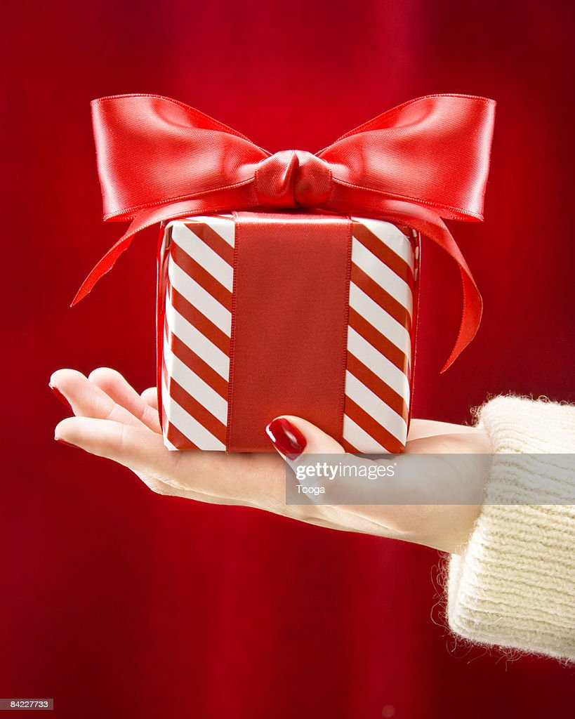 Woman's hand holding red and white present  : ストックフォト