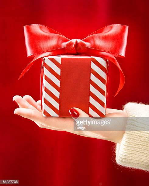 Woman's hand holding red and white present