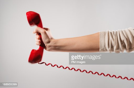 Woman's hand holding red phone