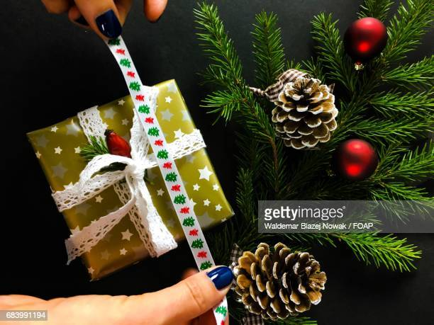 Woman's hand holding ribbon against christmas gift