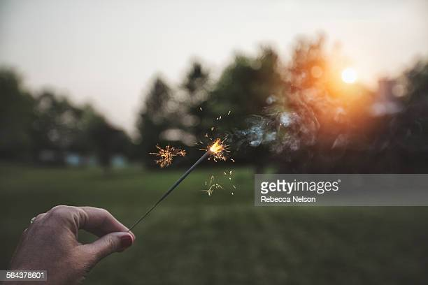 woman's hand holding sparkler