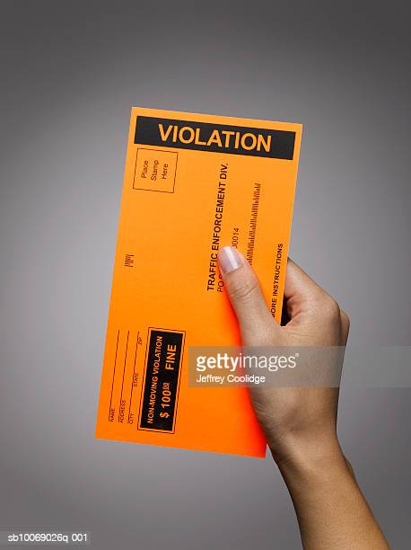 Woman's hand holding violation ticket, studio shot