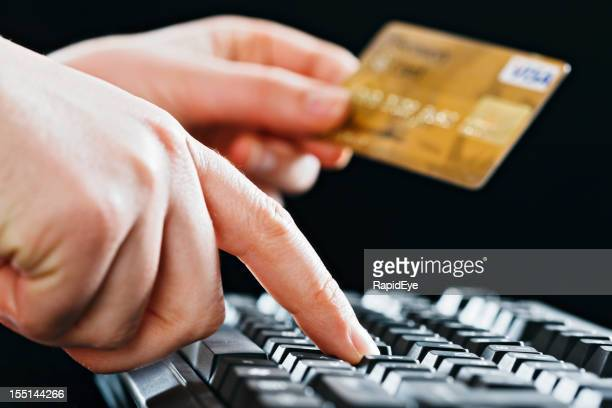 Woman's hand holds credit card and enters data on keyboard