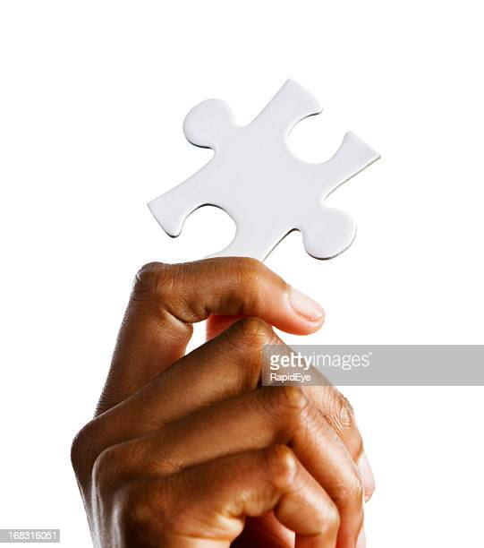 Woman's hand holds up single jigsaw puzzle piece against white