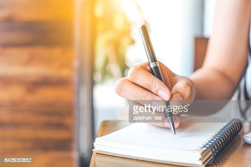 woman's hand is writing on a blank notepad with a pen on a wooden desk. : Stock Photo