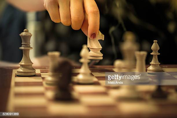 Woman's hand moving a chess piece on a chess board