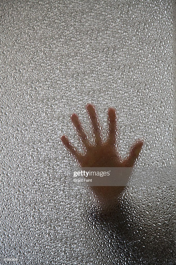 woman's hand on frosted door window : Stock Photo