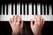 Closeup woman's hand playing piano. Favorite classical music. Top view with dark vignette.
