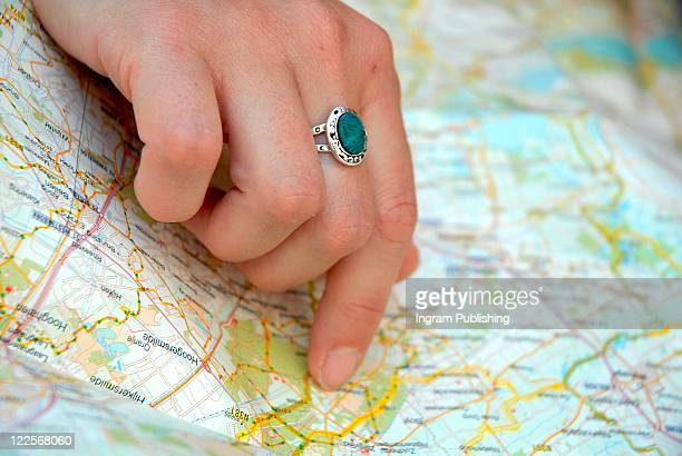 Woman's hand pointing on map