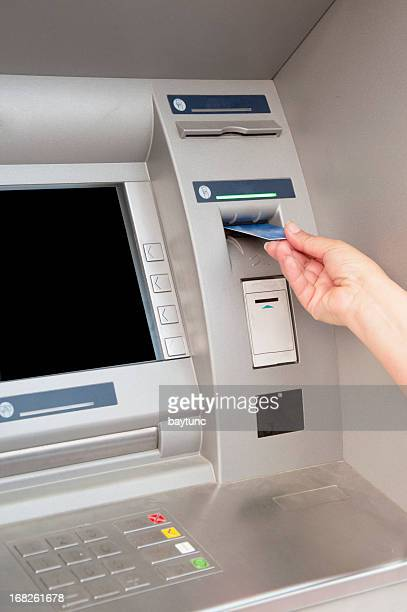 Woman's hand puts bank card into ATM