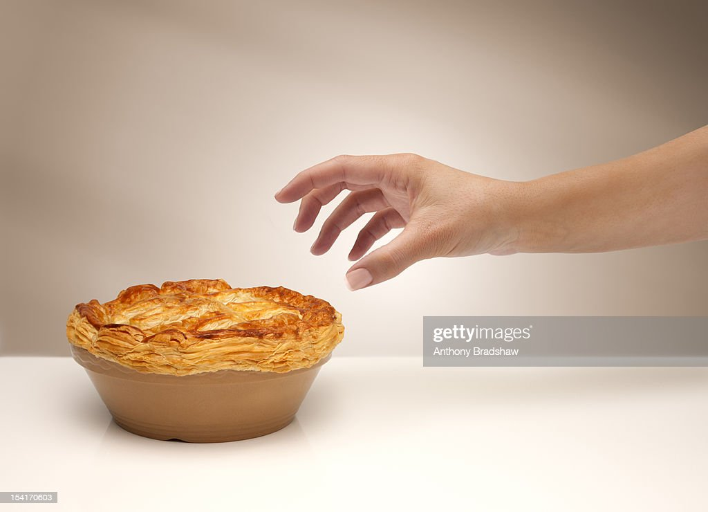 A woman's hand reaching for a pie : Stock Photo