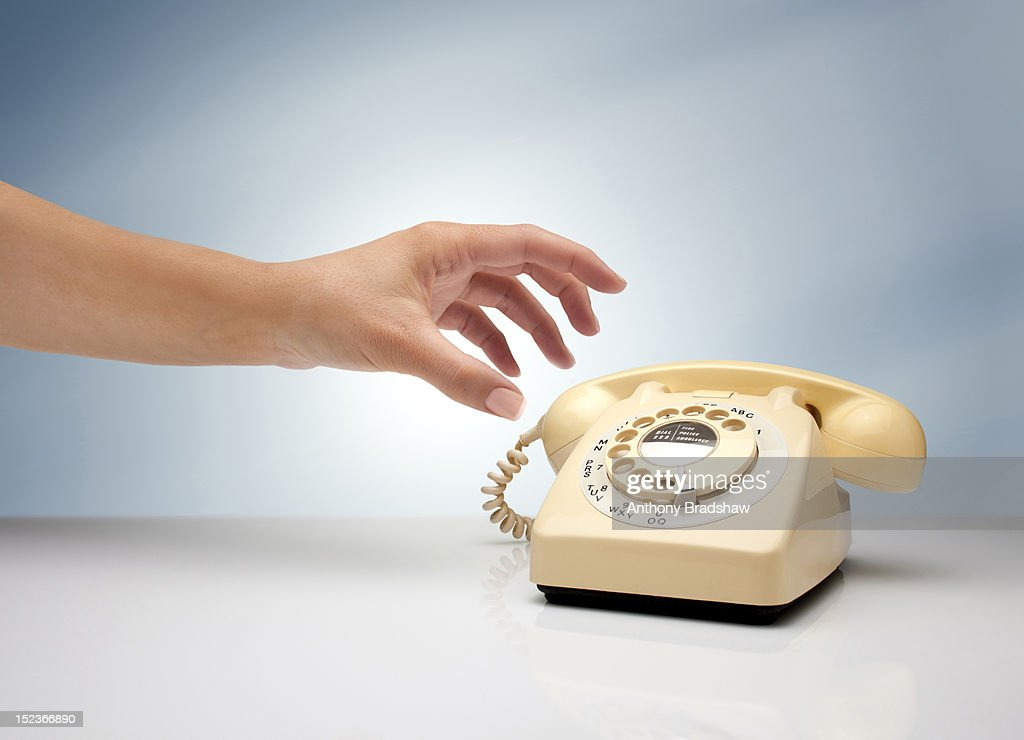 Woman's hand reaching for a retro telephone : Stock Photo