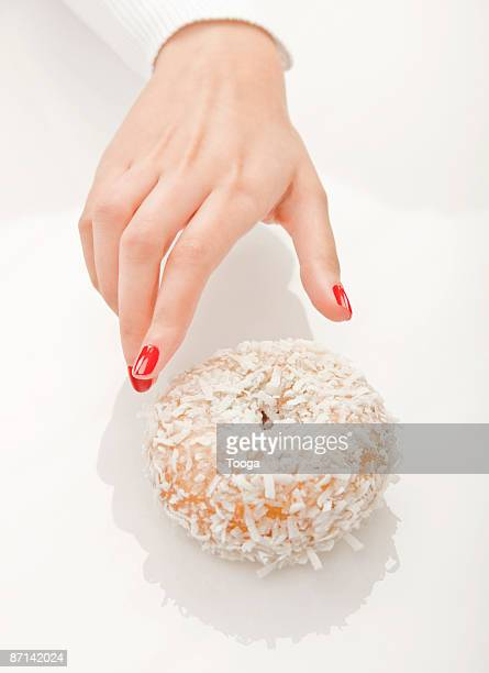 Woman's hand reaching for coconut donut