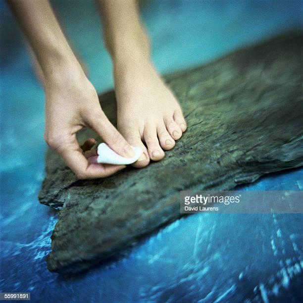Woman's hand removing toenail polish