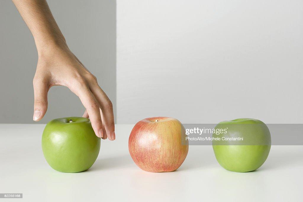 Woman's hand selecting apple