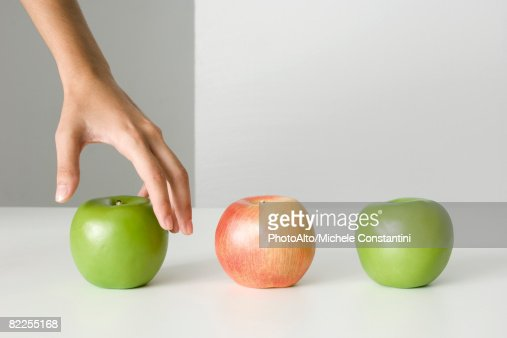 Woman's hand selecting apple