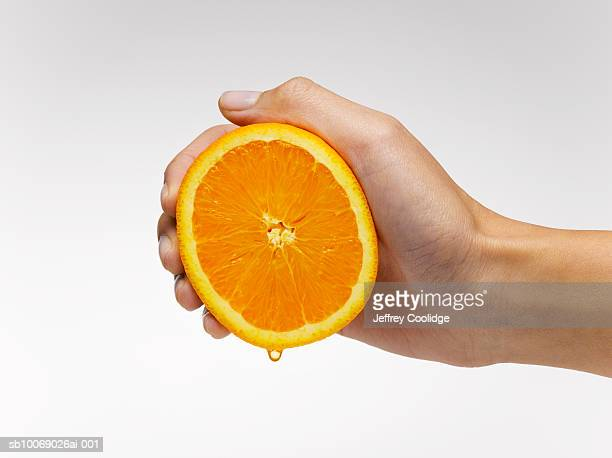 Woman's hand squeezing orange slice, studio shot