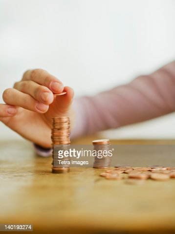 Woman's hand stacking coins, studio shot