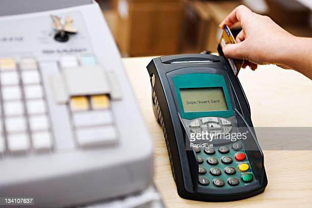 Woman's hand 'swipes' credit card through machine