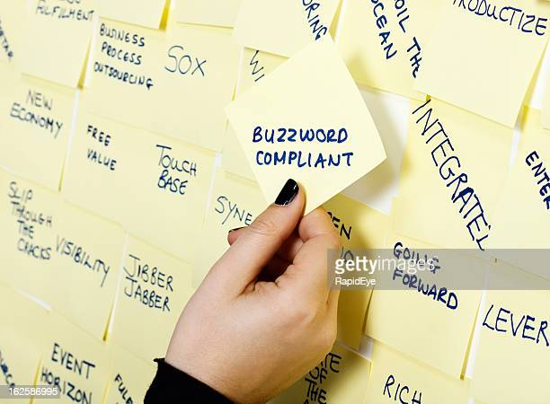Woman's hand takes 'Buzzword Compliant' note from packed noticeboard