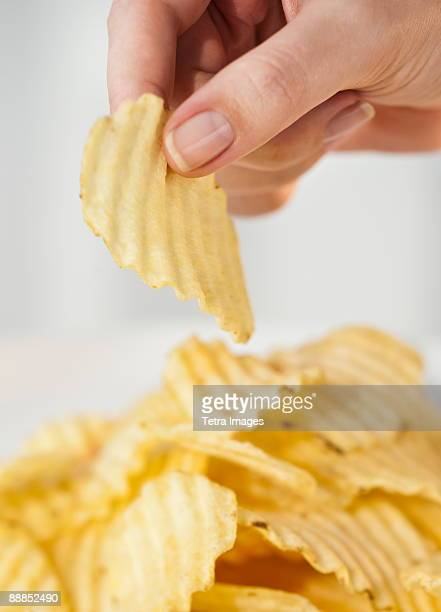 Womans hand taking potato chip