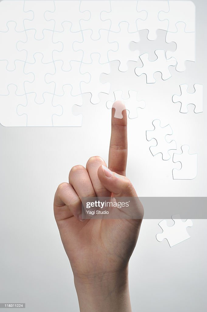 A woman's hand  tapping on Picture puzzle : Stock Photo