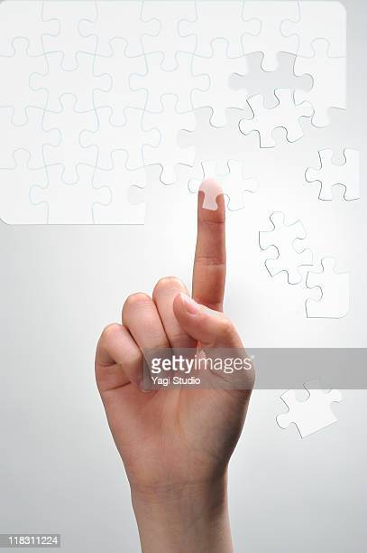 A woman's hand  tapping on Picture puzzle