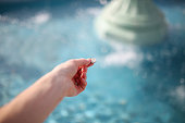 The hand of a woman is holding a coin, about to throw it in the water of a wishing fountain.