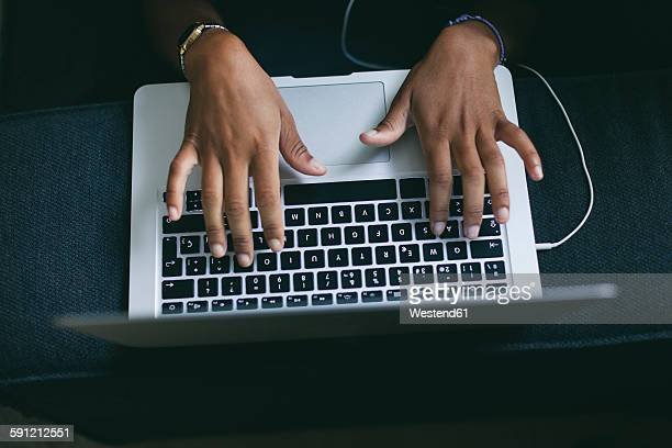 Womans hand typing on keyboard of laptop