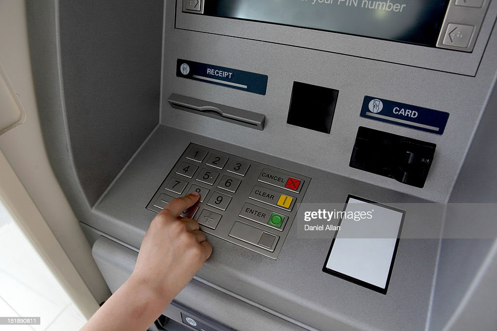 A woman's hand using a cash machine (ATM) : Stock Photo