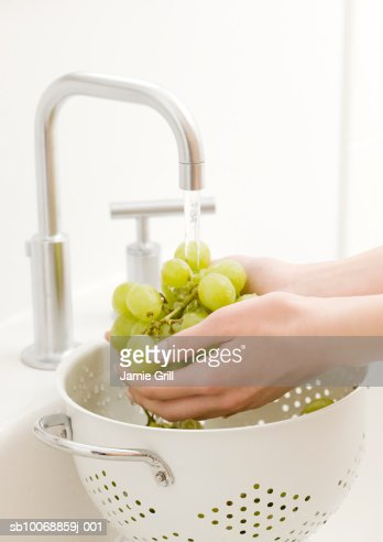 Woman's hand washing grapes in kitchen sink : Stock Photo