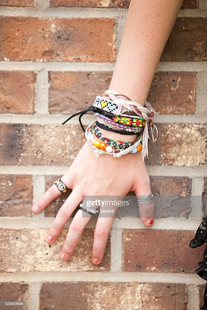 Woman's hand with bracelets by brick wall